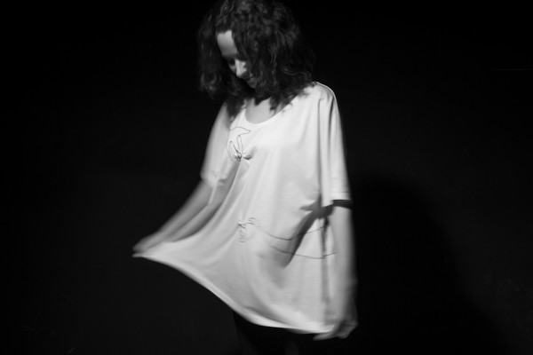 Oversize tee. Two hands pinching the fabric. Entirely embroidered in stem stitch.
