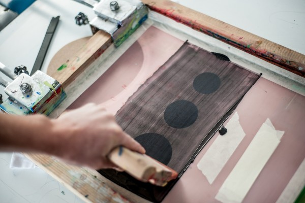 squeegee push ink through the exposed screen